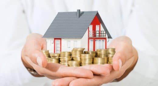 une maison et des pièces dans les mains